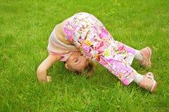 Het meisje maakt oefening op gras