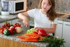 Het meisje maakt salade Stock Foto's