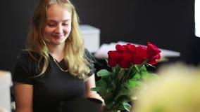 Het meisje maakt verpakking voor rozen in de bloemwinkel stock videobeelden