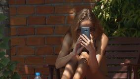 Het meisje maakt Video Gebruikende Telefoonzitting onder Luifel stock video