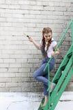 Het meisje maakt het voorbereidingen treffen voor het schilderen van een houten oppervlaktegazebo, omheining royalty-vrije stock fotografie