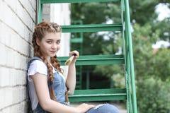 Het meisje maakt het voorbereidingen treffen voor het schilderen van een houten oppervlaktegazebo, omheining stock foto's