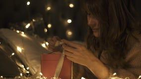 Het meisje maakt wensen en opent een pakket van de Kerstmisgift Concept Kerstmisvakantie en nieuw jaar stock footage
