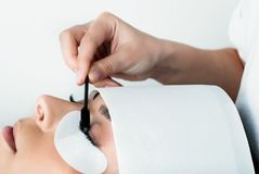 Het meisje maakt zijdewimpers in een schoonheidssalon stock foto's