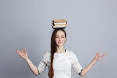 Het meisje mediteert met een stapel van boeken op hoofd royalty-vrije stock afbeeldingen