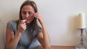 Het meisje meet lichaamstemperatuur en lijdt aan hitte en migraines stock videobeelden