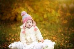 Het meisje met Benedensyndroom rust in de herfstpark Stock Afbeelding