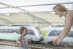 Het meisje met blauwe ogen en blond haar loopt gelukkig langs platfo stock foto
