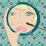 Het meisje doet make-up in de spiegel Stock Fotografie