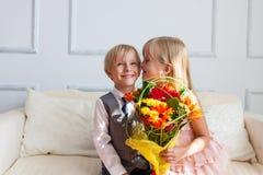 Het meisje met bloemen kust jongen Stock Afbeeldingen