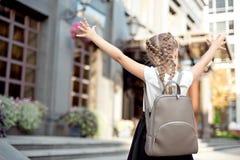 Het meisje met blond haar verheugt zich in erachter het terugkeren naar school van stock foto