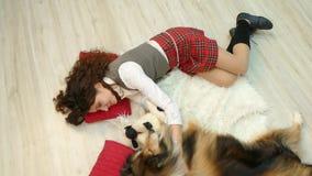 Het meisje met de hond ligt op de vloer stock footage