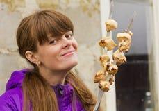 Het meisje met de kebab op vleespennen op de achtergrond van een tuinloods Royalty-vrije Stock Afbeeldingen
