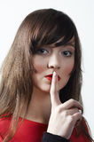 Het meisje met de vinger die aan lippen wordt ingesloten Stock Afbeelding