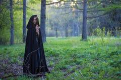 Het meisje met de zwarte mantel in het bos royalty-vrije stock afbeelding