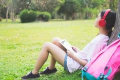 Het meisje met draadloze hoofdtelefoons luistert aan de muziek in park stock afbeelding