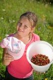 Het meisje met een emmer met een aardbei Stock Fotografie