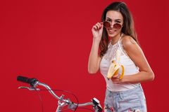 Het meisje met een glimlach met haar glazen op de rode achtergrond Royalty-vrije Stock Foto