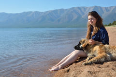 Het meisje met een hond is op de kust van Meer Baikal Stock Afbeelding
