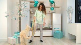 Het meisje met een hond speelt met een hoepel in ruimte met Kerstmisdecoratie stock videobeelden