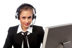 Het meisje met een hoofdtelefoon werkt bij de computer stock foto's