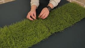 Het meisje met een klok op zijn hand niet stukken die van kunstmatig gras op de vloer liggen Close-up van de handen van het meisj stock footage