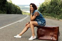 Het meisje met een koffer houdt de auto op de weg tegen royalty-vrije stock afbeelding