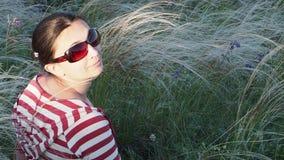 Het meisje met een lange vlecht in zonnebril stock videobeelden