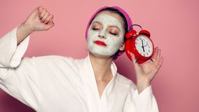 Het meisje met een masker op zijn gezicht houdt een klok in zijn hand op een roze achtergrond Concept huidzorg stock videobeelden
