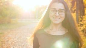 Het meisje met een mooie glimlach gaat naar de camera en het glimlachen Stralen van de de herfst de bos Mooie zon Close-up stock video