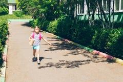 Het meisje met een roze rugzak en een document zak met een beet gaat naar school Het concept van de school Horizontaal kader royalty-vrije stock afbeelding