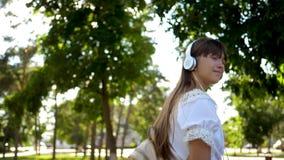 Het meisje met een rugzak gaat in hoofdtelefoons parkeren en luistert aan muziek en glimlachen, tiener gelukkig golven zijn hand  stock video