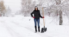 Het meisje met een schop maakt de sneeuw schoon royalty-vrije stock afbeeldingen