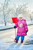 Het meisje met een schop voor sneeuw royalty-vrije stock afbeelding