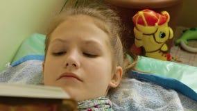 Het meisje met een sjaal op hals leest in bed en hoest stock footage