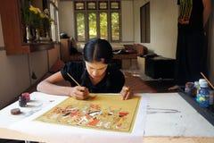 Het meisje met een traditioneel verfraaid gezicht schildert een beeld van zand op de stof Stock Afbeeldingen