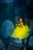 Het meisje met een viool onder water stock foto's