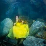 Het meisje met een viool onder water stock foto