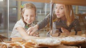 Het meisje met een vlecht en haar mama bekijken de pastei in venster het kiezen stock foto's