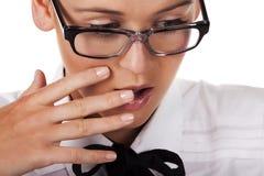 Het meisje met glazen behandelt mond met zijn hand Stock Foto's