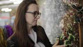 Het meisje met glazen bij de supermarkt kiest een Kerstmiskroon stock videobeelden