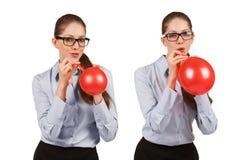 Het meisje met glazen blaast een rode ballon op stock afbeelding