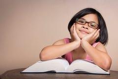 Het meisje met glazen het lezen en kijkt gelukkig Stock Fotografie