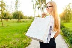 Het meisje met glazen, kleedde zich in een witte t-shirt, houdend een aankoop terwijl in het Park stock afbeelding