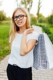 Het meisje met glazen, kleedde zich in een witte t-shirt, houdend purchas stock afbeeldingen
