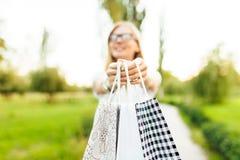 Het meisje met glazen, kleedde zich in een witte t-shirt, houdend purchas stock foto's