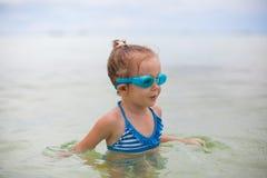 Het meisje met glazen voor het zwemmen zwemt en Stock Foto