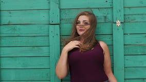 Het meisje met grote vormen leunt op een groene houten muur in de zomer in Park stock videobeelden