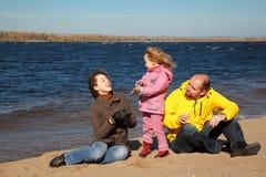 Het meisje met haar ouders speelde op strand Stock Afbeeldingen