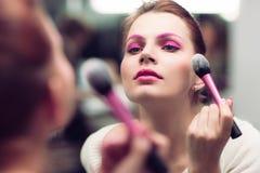 Het meisje met helder roze een samenstelling schrijft bloost in stock afbeelding